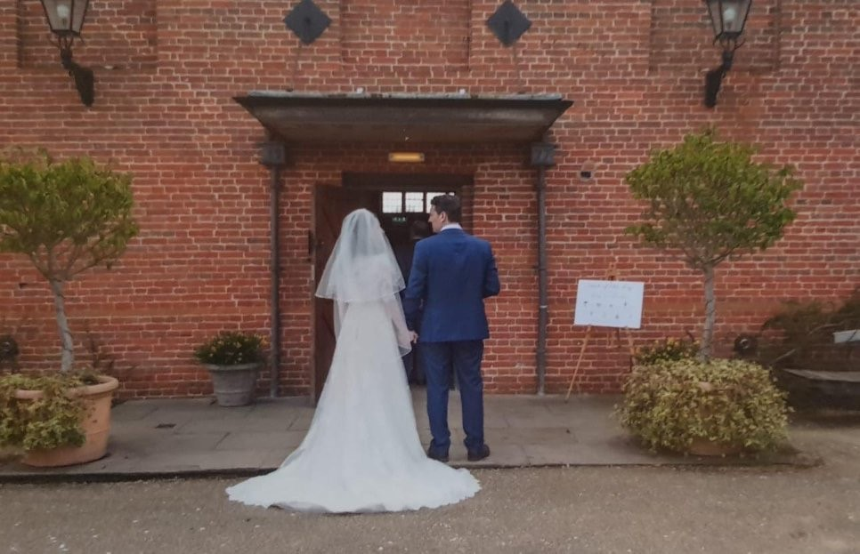 Bride and groom enter Suffolk barn wedding venue
