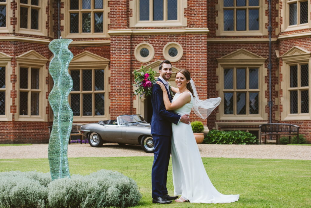 Bride and groom in front of Haughley Park manor house